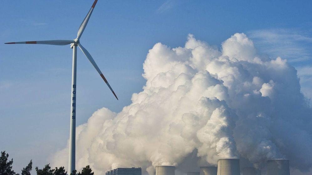 Foto: Una turbina de energía eólica, enfrente de las torres de una planta de energía. (EFE)