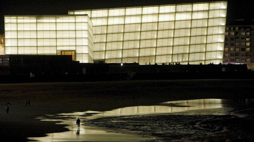 Foto: Varias personas pasean por la playa de la Zurriola de San Sebastián con el Kursaal iluminado. (EFE)