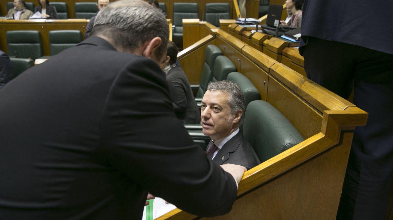 Iñigo Urkullu conversa con un compañero de grupo al comienzo del pleno de control en el Parlamento vasco. (EFE)