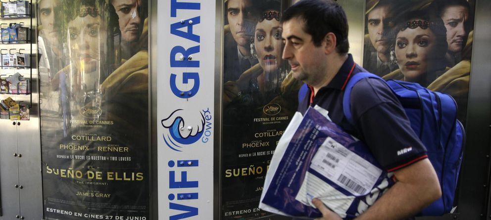 Foto: A man walks past a newspaper kiosk advertising spanish wireless network provider gowex in madrid