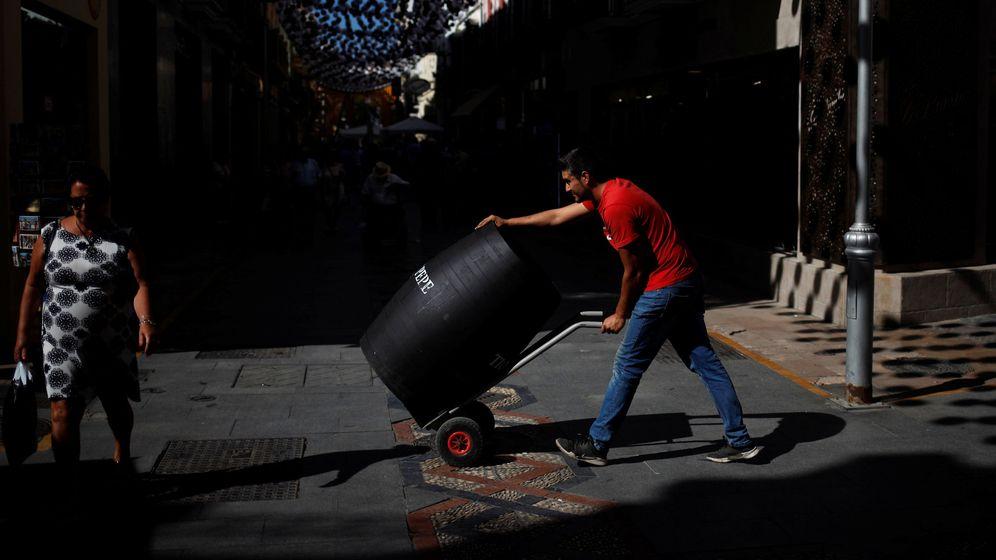 Foto: Un trabajador carga con un barril en Málaga. (Reuters)