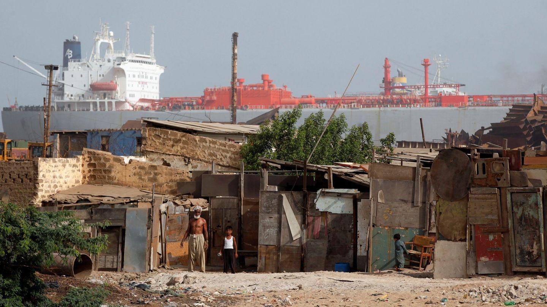 Un empleado de desguaces de barcos, a la puerta de su infravivienda en Gadani (Pakistán) junto a un hijo suyo. (Reuters)