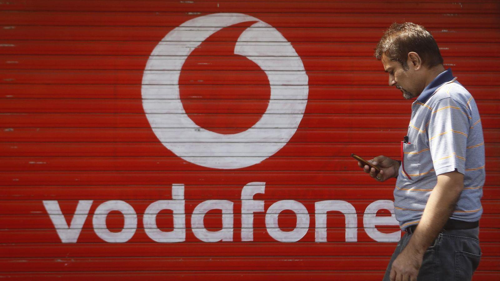 Foto: Un hombre comprueba el móvil delante de una tienda de Vodafone. (Reuters)