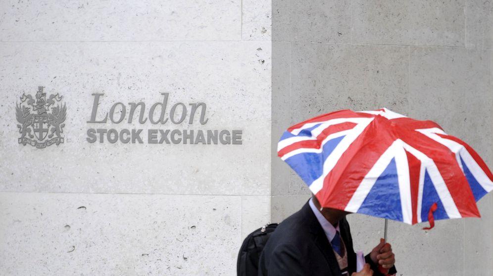Foto: Un hombre se cubre de la lluvia a su paso por la Bolsa de Londres. (Reuters)