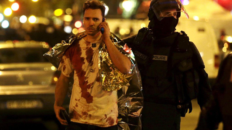 Foto: Un policía asiste a uno de los heridos cerca de la sala de conciertos Bataclan. (Reuters)