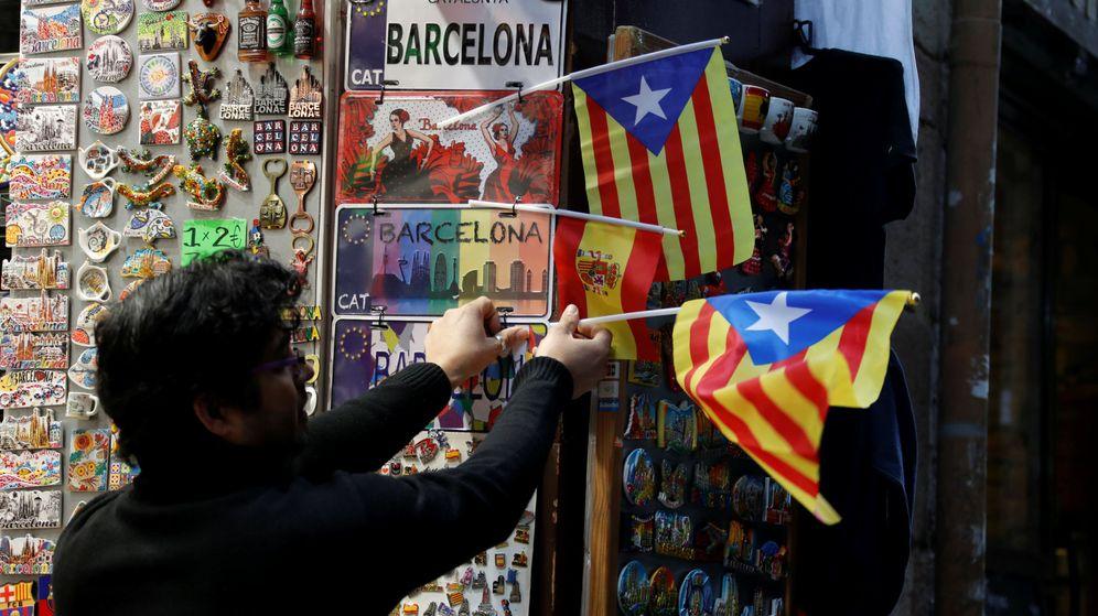 Foto: Un empleado de una tienda coloca una estelada en Barcelona. (Reuters)