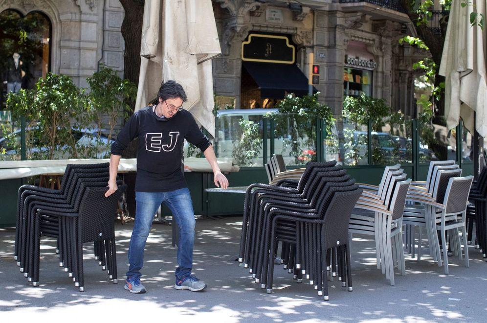 Foto: Un trabajador de un restaurante del centro de Barcelona prepara la terraza, este 22 de mayo, para la apertura a partir del lunes 25. (EFE)