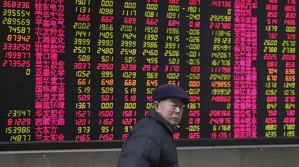Foto: Un inversor pasa delante de una pantalla con información bursátil. (EFE)