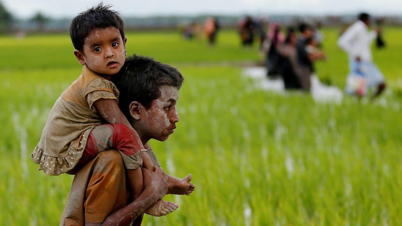 Foto: Un niño rohingyá carga con un pequeño mientras cruzan la frontera en Teknaf, entre Myanmar y Bangladesh, el 1 de septiembre de 2017. (Reuters)