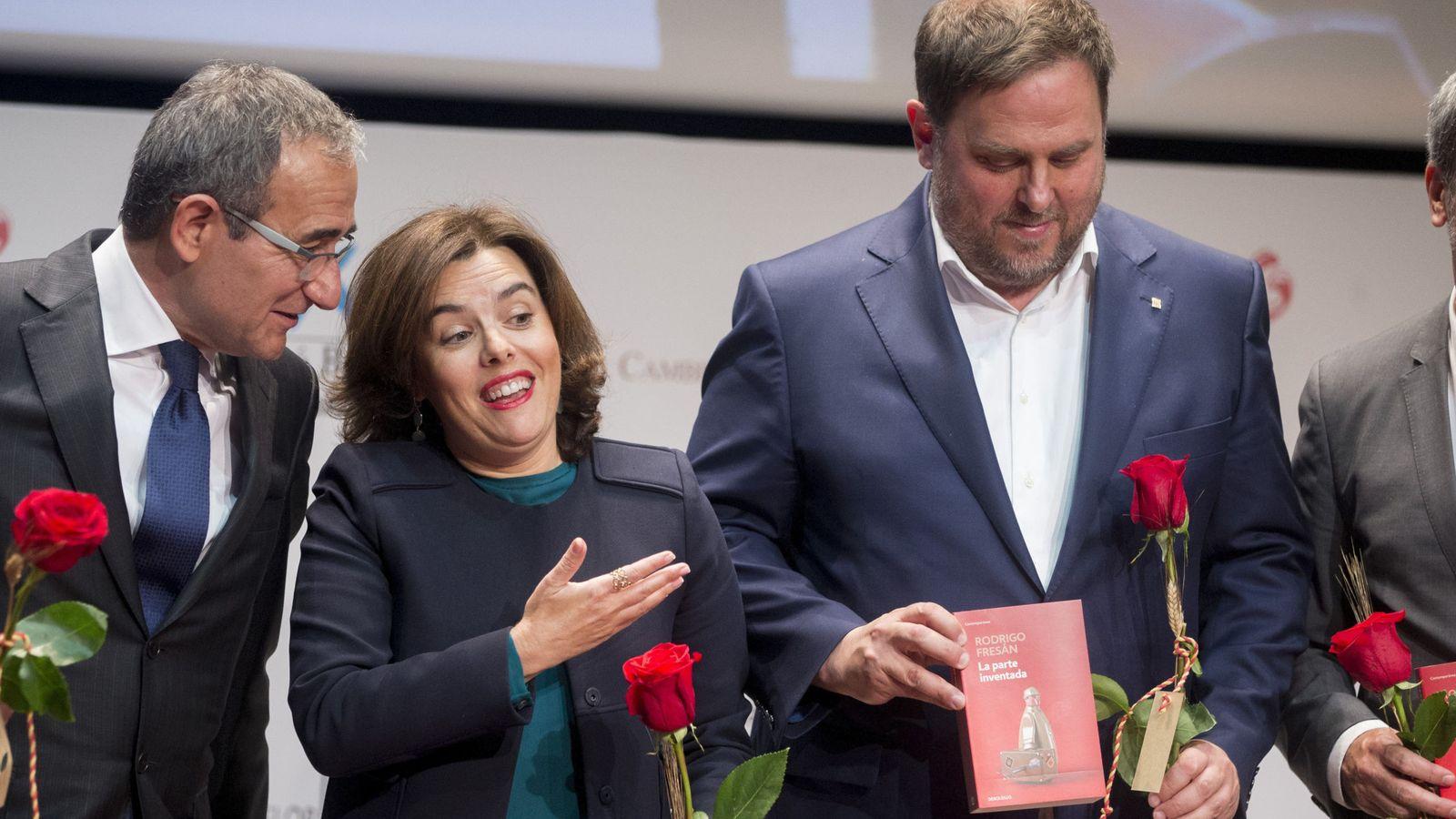 Foto: La vicepresidenta del Gobierno, Soraya Sáenz de Santamaria (c) regala un libro al vicepresidente de la Generalitat de Cataluña, Oriol Junqueras (d), en presencia del presidente del Gremio de Editores, Patrici Tixis. (EFE)