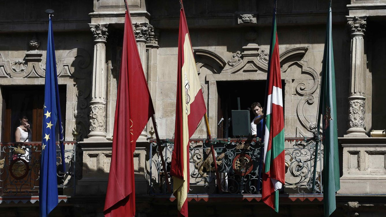 Foto: Las cuatro banderas oficiales y la ikurriña en el balcón del Ayuntamiento de Pamplona. (EFE)