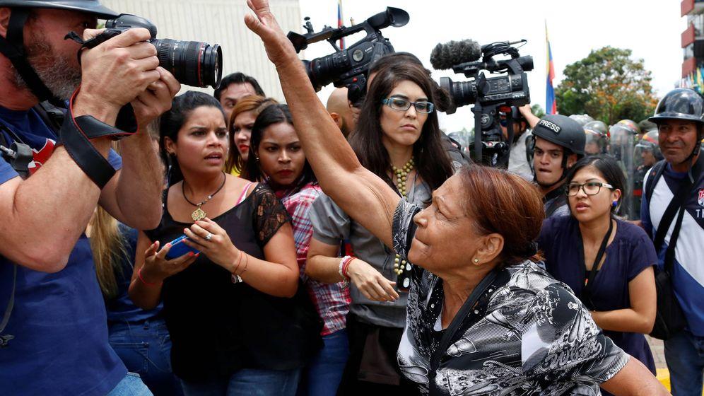 Foto: Una partidaria del Gobierno intenta arrebatarle la cámara a un fotógrafo durante enfrentamientos frente a la sede del Tribunal Supremo en Caracas, en marzo de 2017. (Reuters)