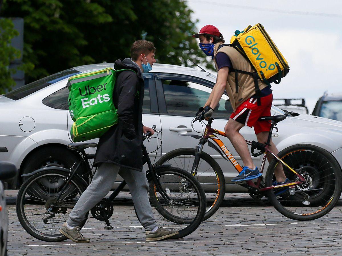 Foto: Un 'rider' de Uber Eats y uno de Glovo se cruzan en la calle. (Reuters)