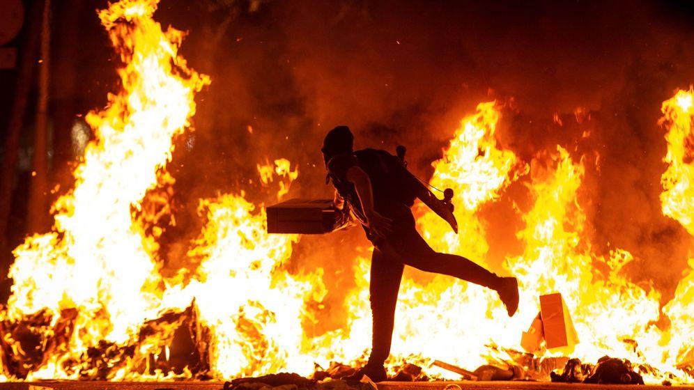 Foto: Un manifestante echa al fuego un cartón junto a la Delegación del Gobierno en Barcelona. (EFE)