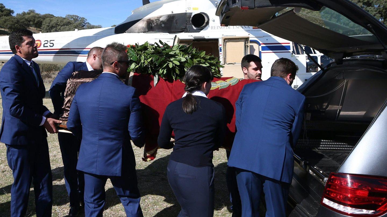 Operarios meten el féretro con los restos de Francisco Franco en el coche fúnebre tras el aterrizaje del helicóptero al Monte de El Pardo. (EFE)