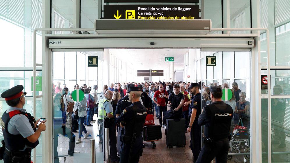 Foto: Agentes de los Mossos d'Esquadra y de la Policía Nacional controlan el acceso de personas a la terminal 1 del Aeropuerto de El Prat. (EFE)