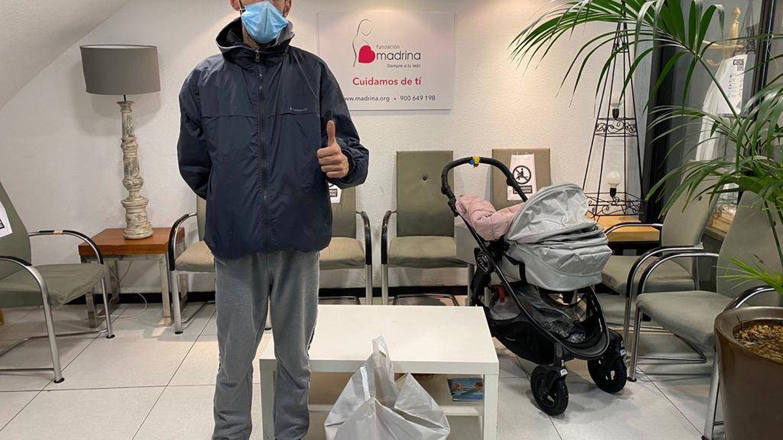 Manuel, parado y sin la ayuda del IMV, recogiendo víveres junto a su bebé. (F. Madrina)