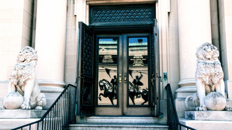 Foto: La entrada a la sede, con el reflejo de la estatua de El Cid en el cristal de las puertas.