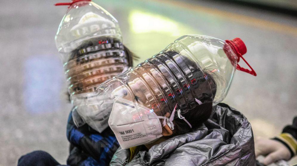 Foto: Dos niños se 'protegen' del coronavirus con botellas de plástico. (EFE)