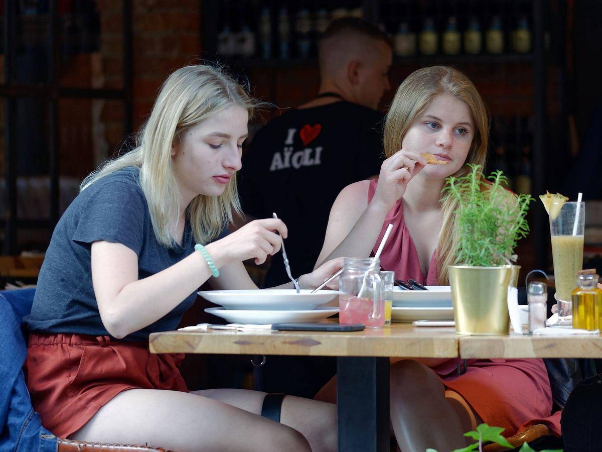 Foto: Dos chicas comen en una terraza de un bar. (Pixabay)