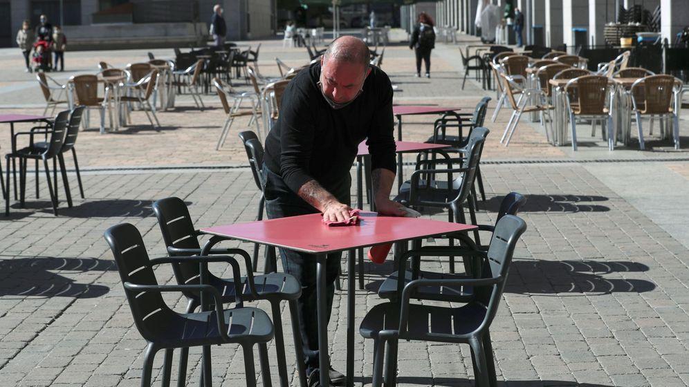Foto: Un camarero desinfenta la mesa de una terraza. (EFE)