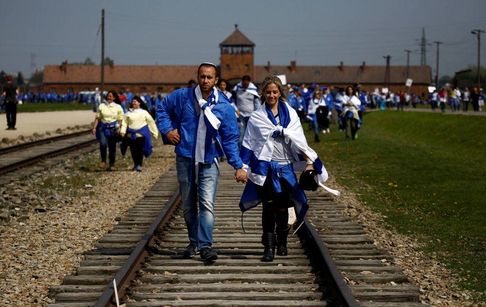 Foto: Una pareja camina sobre la vía de tren en el campo de concentración de Auschwitz-Birkenau, en Brzezinka, Polonia. (Reuters)