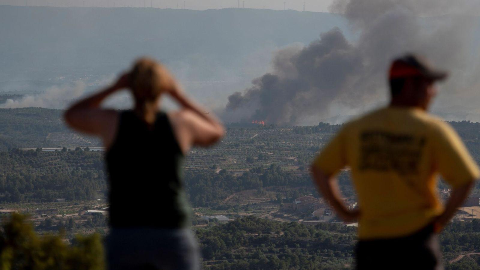 Foto: Vecinos de Bovera observan el avance del fuego en las inmediaciones de la localidad. (EFE)