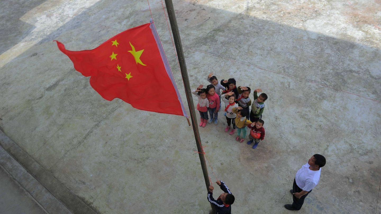 Alumnos chinos de primaria durante una ceremonia de izado de bandera en un colegio de Longli, provincia de Guizhou. (Reuters)