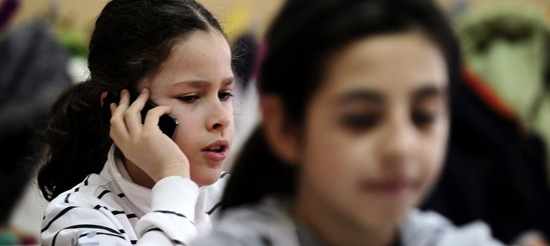 Foto: Dos niñas utilizan su teléfono móvil durante una clase (Reuters)