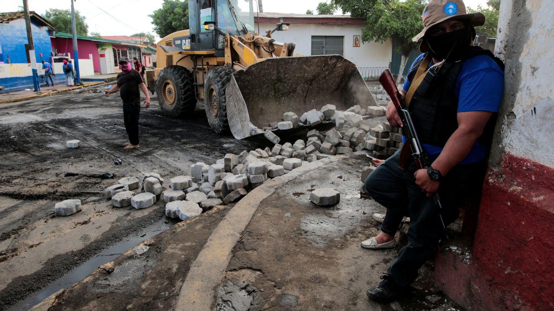 Un partidario del Gobierno de Ortega monta guardia mientras desmantelan unabarricada en Monimbo, Masaya, el 17 de julio de 2018. (Reuters)