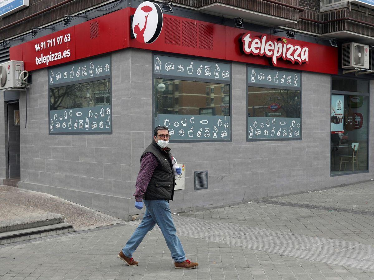 Foto: Un hombre camina frente a un local de Telepizza en Madrid. (EFE)