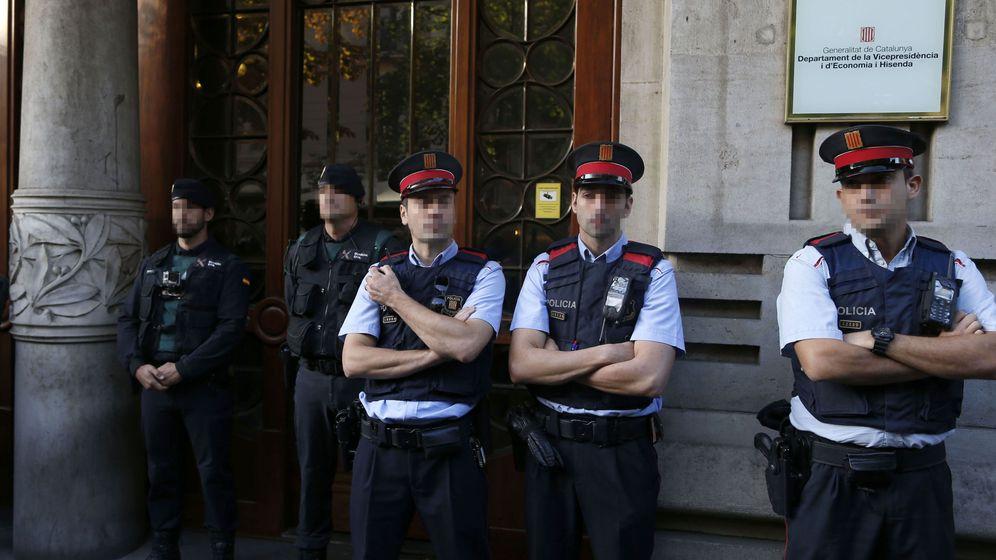 Foto: Agentes de la Guardia Civil y de los Mossos d'Esquadra en la puerta de la consellería de Economía. (EFE)