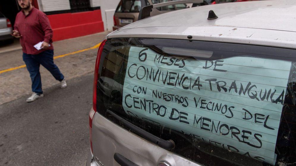 Foto: Un coche con un cartel estacionado en la calle del barrio de la Macarena de Sevilla, donde está ubicado un centro de menores. (EFE)