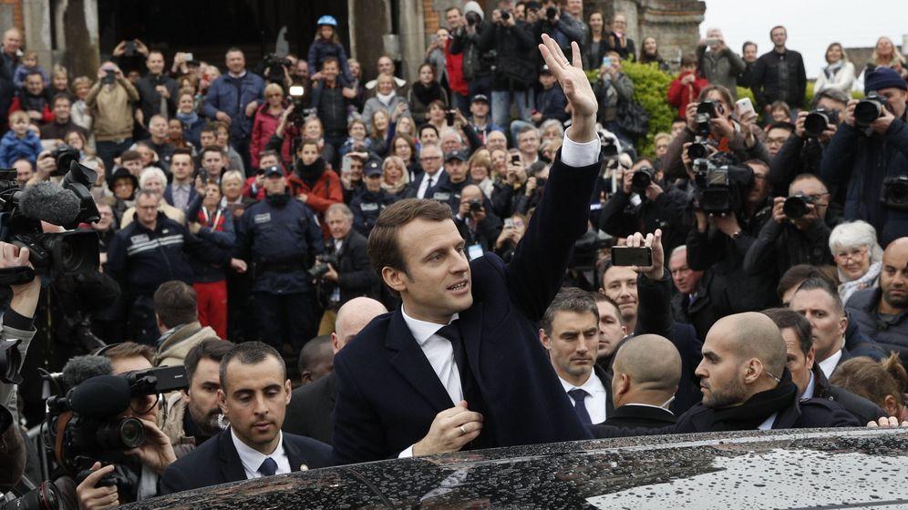 Foto: El candidato Emmanuel Macron (C) saluda a los ciudadanos tras ejercer su derecho al voto. (EFE)