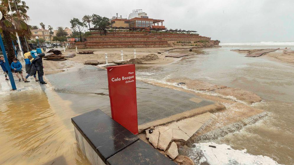 Foto:  Varias personas observan los daños causados en la Playa Cala Bosque. (EFE)