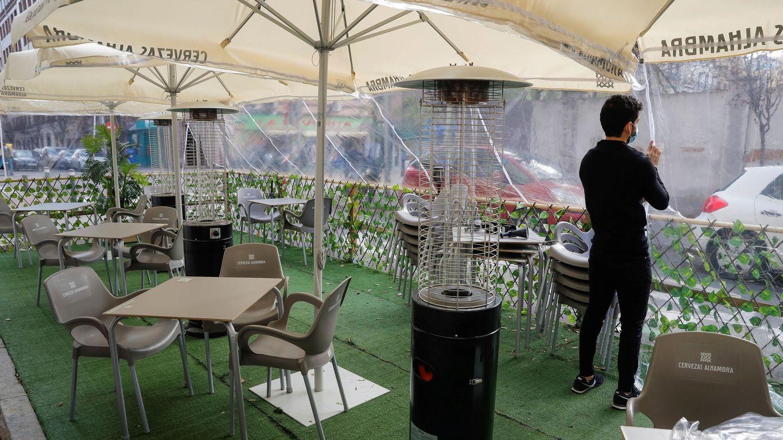 Un camarero prepara su terraza sobre una plaza de aparcamiento. (EFE)