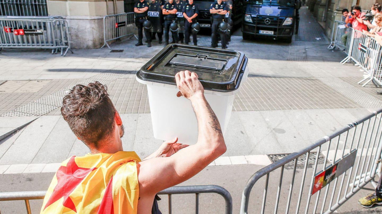 Un joven muestra una urna empleada el 1-O a los policías apostados en la Via Laietana, en Barcelona. (EFE)