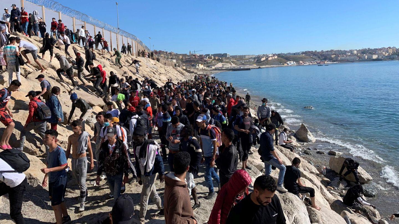 Un grupo de personas trata de cruzar la valla fronteriza que separa Fnideq (Castillejos, Marruecos) y Ceuta. (EFE)