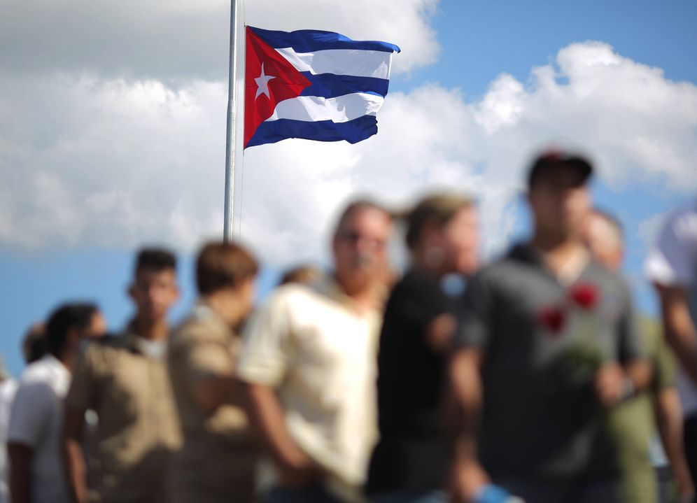 Foto: Una bandera cubana sobre un grupo de personas que esperan para rendir tributo al difunto Fidel Castro. (Reuters)