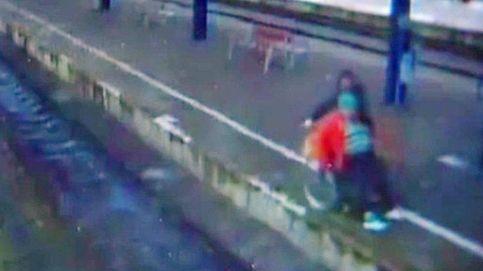 Un hombre empuja a una mujer en silla de ruedas a las vías del tren