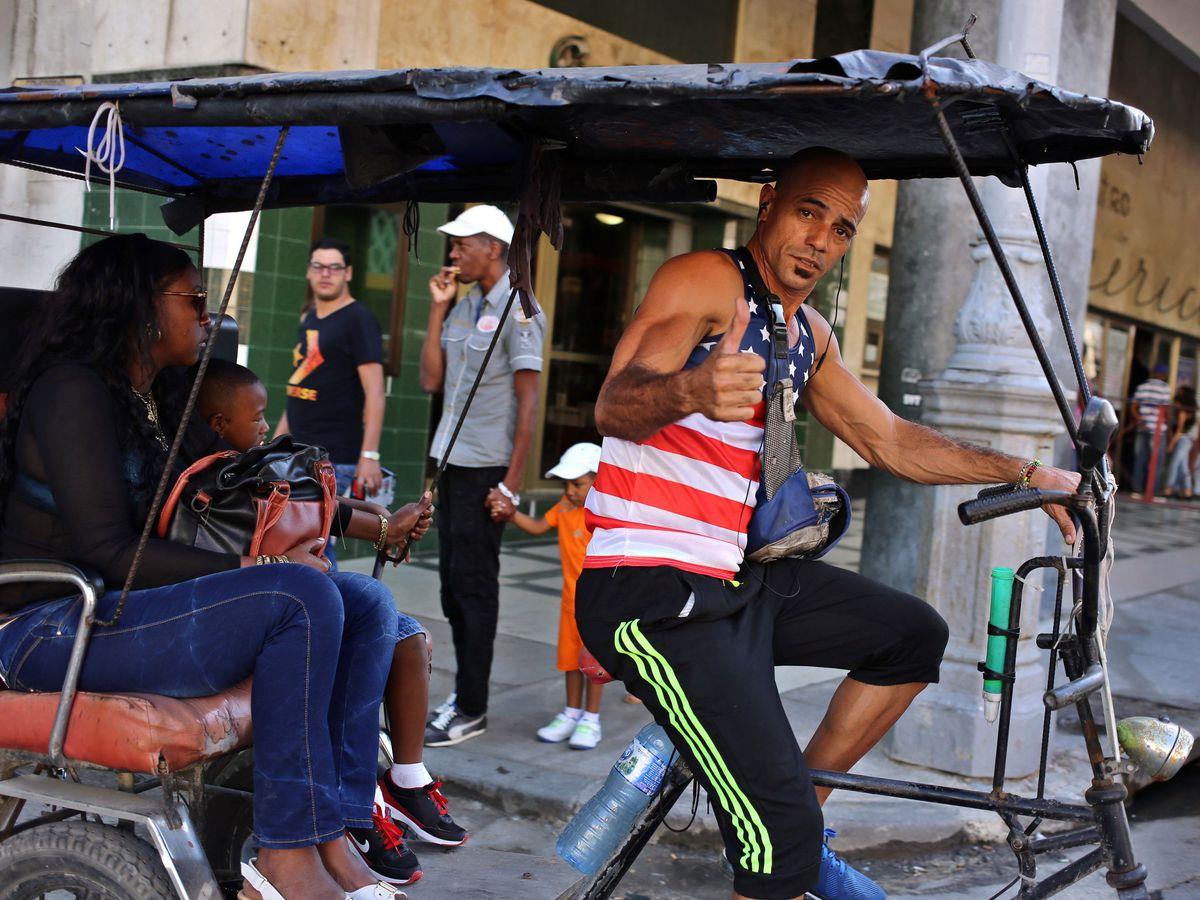 Foto: Un hombre vestido con una camiseta con la bandera de EEUU maneja un 'bicitaxi' en La Habana. (EFE)