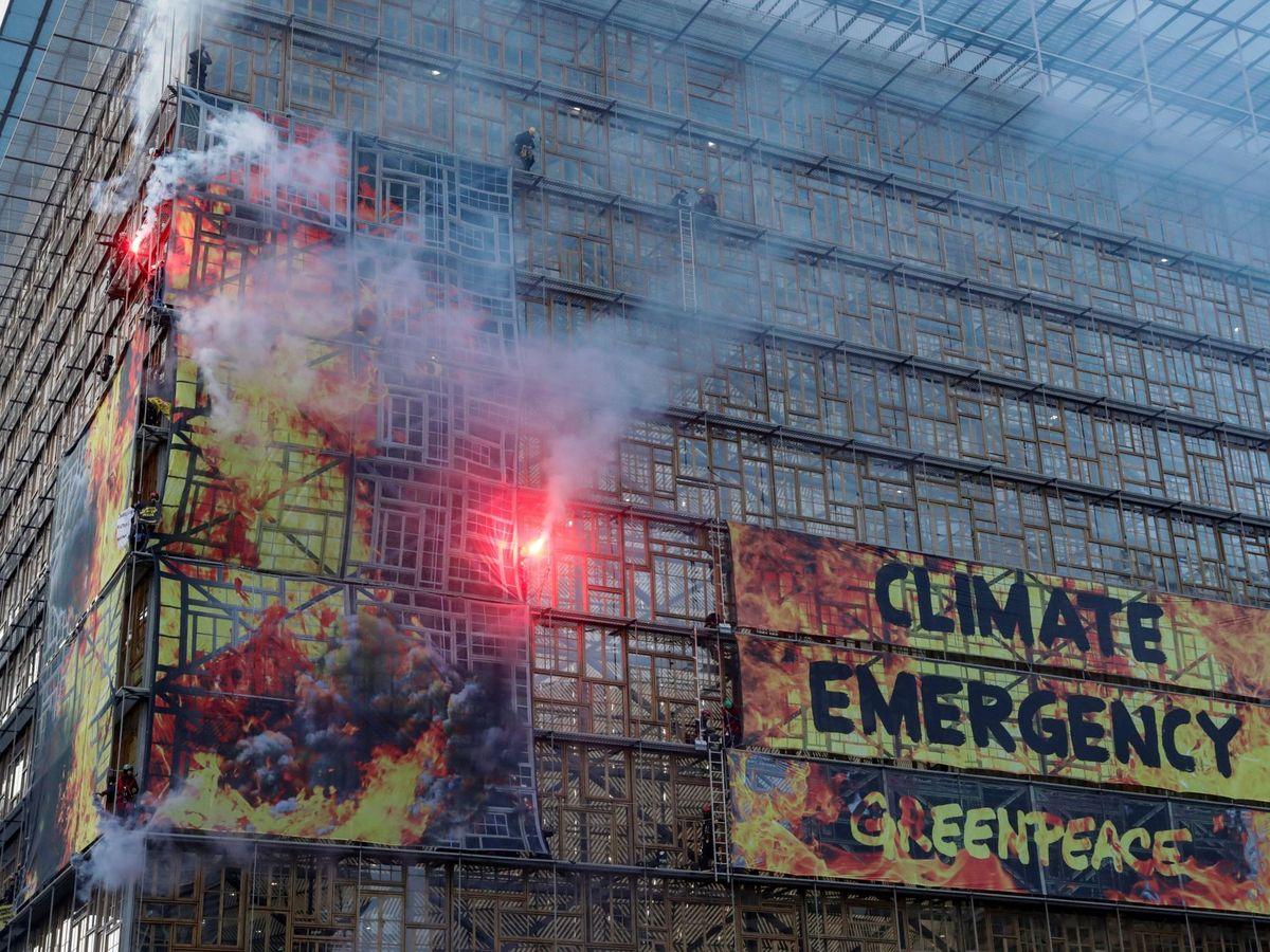 Foto: Activistas medioambientales cuelgan una pancarta gigante para anunciar la emergencia climática. (Reuters)