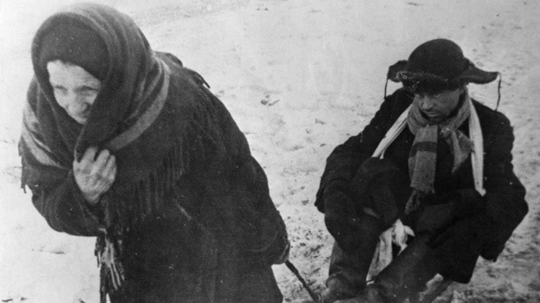 Una pareja mendiga por Leningrado tras el bombardeo. (Israel Ozerskiy / https://www.tassphoto.com/ru)