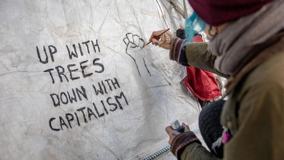 Foto: Activistas escriben arriba con los árboles, abajo con el capitalismo en unas protestas en Berlín. (Reuters)