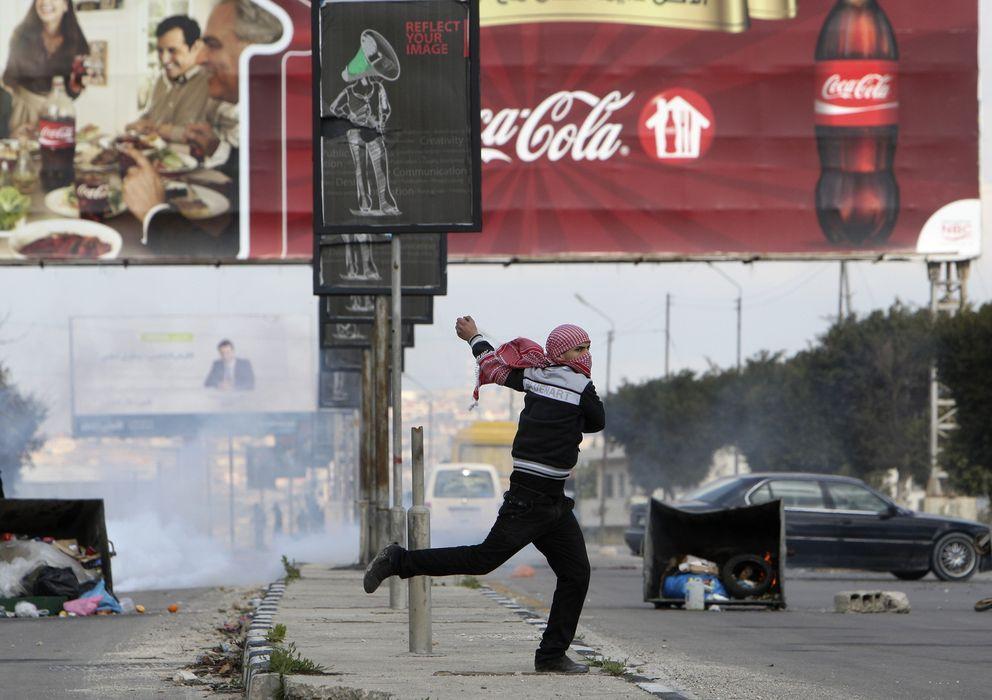 Foto: Un palestino lanza una piedra contra un agente israelí y de fondo se ve un cartel con publicidad de Coca-Cola (Reuters)