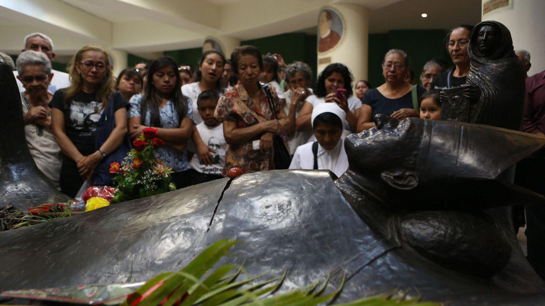 Varias personas rezan frente a la tumba del arzobispo Óscar Arnulfo Romero, en San Salvador, cuando se cumplen 37 años de su homicidio. (Efe)