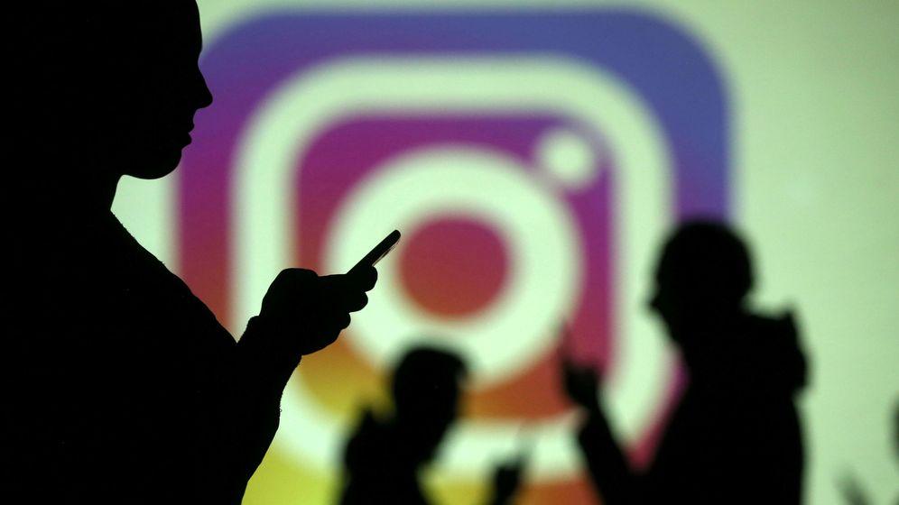 Foto: Usuarios de teléfonos móviles junto al logo de Instagra. (Reuters)