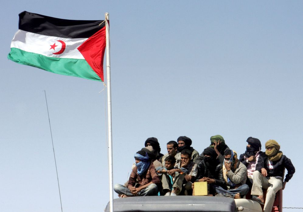 Foto: Un grupo de saharauis occidentales, junto a la bandera del territorio. (EFE)
