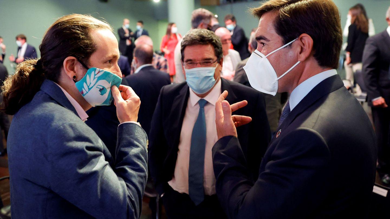 El vicepresidente del Gobierno, Pablo Iglesias, conversa con el presidente del BBVA, Carlos Torres, junto con el ministro de Seguridad Social, José María Escrivá. (EFE)