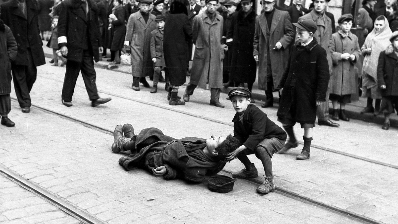 Foto: Un niño ayuda a un hombre desmayado en las vías por las que pasaba el tranvía que salía del gueto en 1941. (Cordon Press)